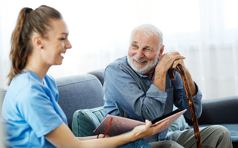 senior male smiling with laughing nurse