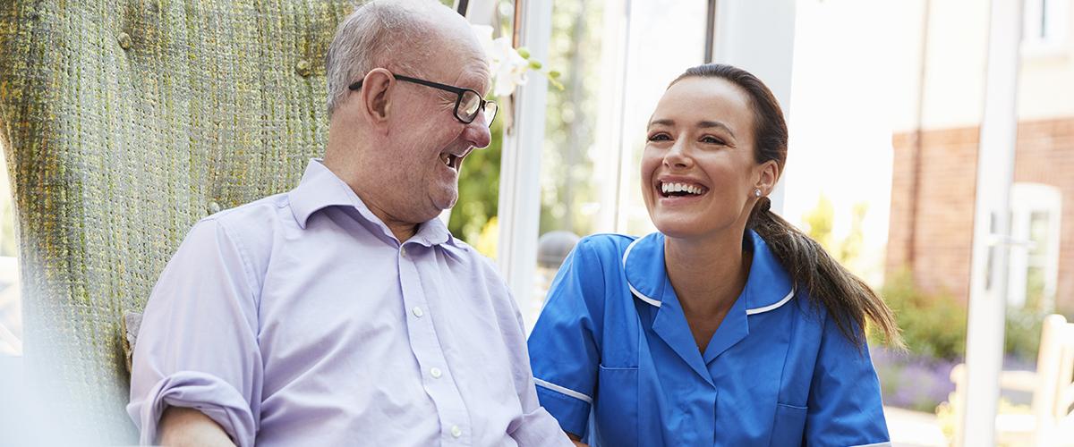 senior man and young female caretaker laughing