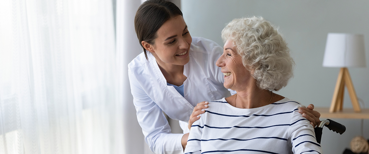 female caretaker and senior woman in wheelchair smiling